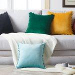 Poduszka dekoracyjna z pomponami – jasnoszara